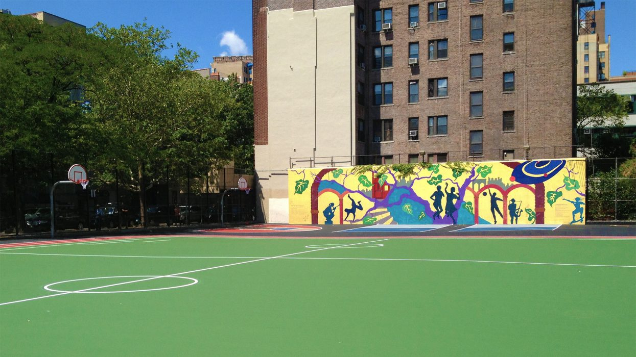 View of colorful playground/athletic field surface and mural on wall