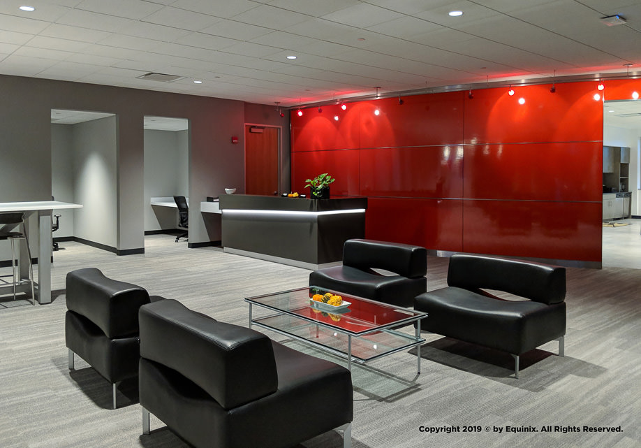 """Lounge interior with seating and red """"silo"""" wall"""
