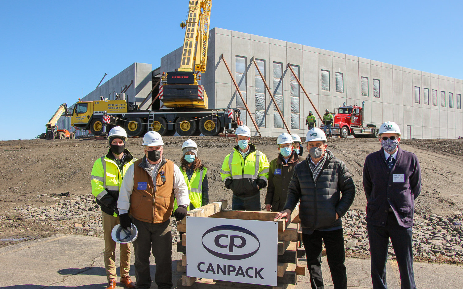 Group of constructors and consultants in front of construction site